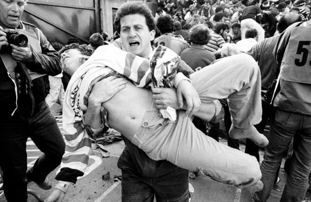 An injured soccer fan is carried to safety by a friend after a wall collapsed during violence between fans before the European Cup final between Juventus and Liverpool at the Heysel stadium in Brussels, May 29, 1985. 39 people died, and a further 600 were injured. (Photo by Nick Didlick/Reuters)