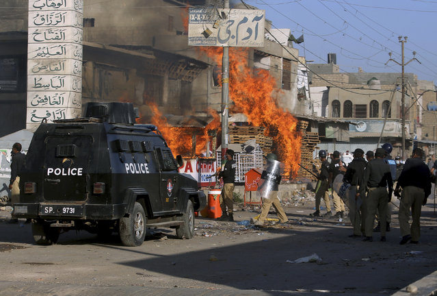 Police officers arrive to confront angry supporters of Tehreek-e-Labiak Pakistan, a radical Islamist political party, who set fires during protests following the arrest of their party leader Saad Rizvi, in Karachi, Pakistan, Tuesday, April 13, 2021. (Photo by Fareed Khan/AP Photo)