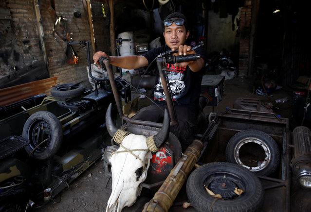 Yogi Hermawan Saifullah, 28, the owner of a workshop that builds extreme Vespas poses for a photograph while sitting on one of his tank Vespa designs at his shop in Kediri, East Java, Indonesia, August 2, 2018. (Photo by Darren Whiteside/Reuters)