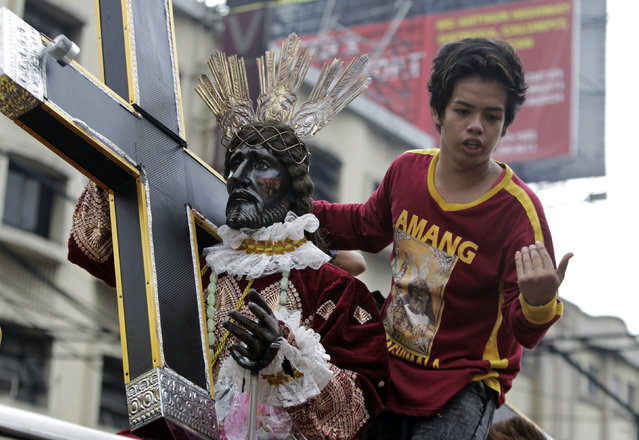 A devotee stands next to a Black Nazarene replica during a procession two days before the annual parade of the Black Nazarene in Manila, Philippines January 7, 2016. (Photo by Janis Alano/Reuters)