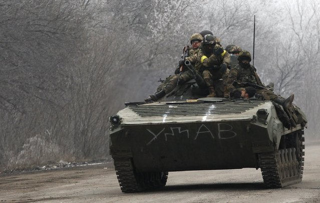 Ukrainian government soldiers ride on an armored vehicle on the road between the towns of Dabeltseve and Artemivsk, Ukraine, Saturday, February 14, 2015. (Photo by Petr David Josek/AP Photo)