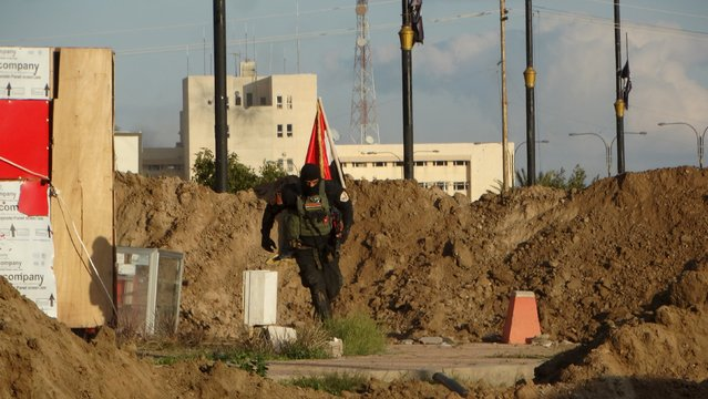 A member of the Iraqi security forces runs after planting an Iraqi flag in the ground, in the city of Ramadi, January 2, 2016. Picture taken January 2, 2016. (Photo by Reuters/Stringer)