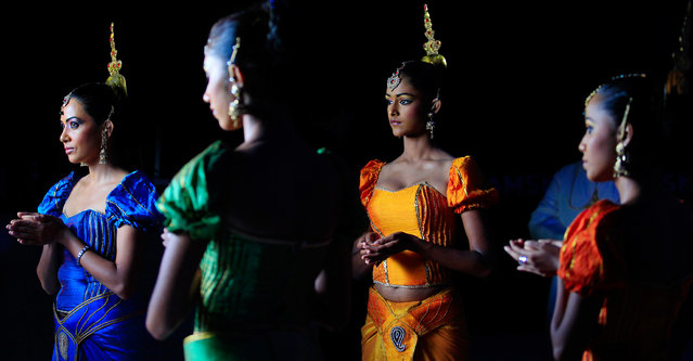 Traditional dancers wait for guests during the Kramaski factory's 20th anniversary celebrations in Katunayake, about 31 km (19 miles) north of Colombo September 27, 2013. (Photo by Dinuka Liyanawatte/Reuters)