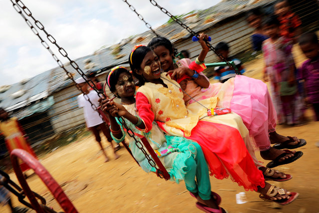 Rohingya refugee children ride on a swing ride on the day of Eid al-Adha in the Kutupalong refugee camp in Cox's Bazar, Bangladesh on August 22, 2018. (Photo by Mohammad Ponir Hossain/Reuters)