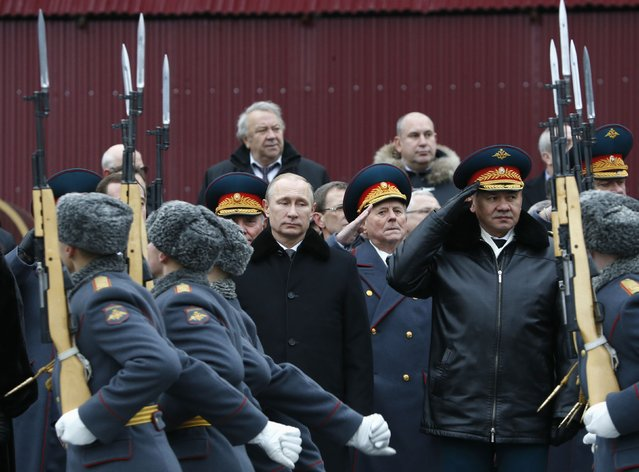 Russian President Vladimir Putin (C) and Defence Minister Sergei Shoigu (R, front row) watch honor guards pass by as they attend a wreath laying ceremony to mark the Defender of the Fatherland Day at the Tomb of the Unknown Soldier by the Kremlin walls in central Moscow February 23, 2015. (Photo by Sergei Karpukhin/Reuters)