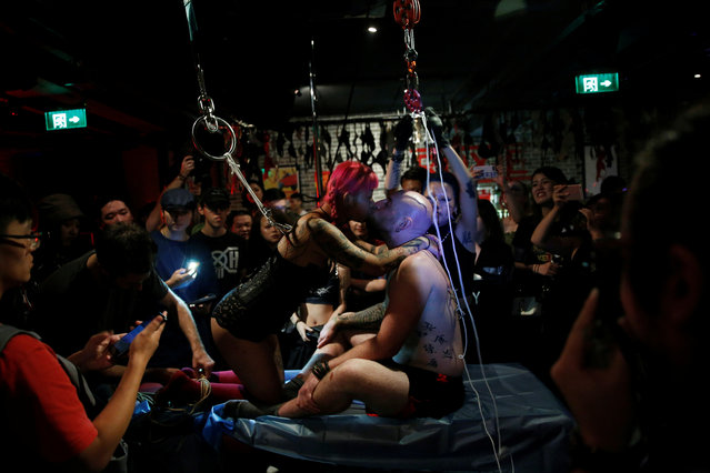 July and her boyfriend Jason Schaller kiss as they wait to be suspended from hooks pierced through their skins by professional body artist Wei Yilaien at a bar in Shanghai, China on September 16, 2018. (Photo by Aly Song/Reuters)