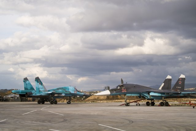 A Russian bomber, left, taxies out for a combat mission while another aircraft stand on the tarmac at Hemeimeem air base in Syria Wednesday January 20, 2016. (Photo by Vladimir Isachenkov/AP Photo)