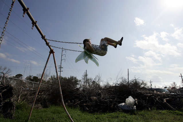 In this February 25, 2006, file photo, Nysa Loudon, 11, swings in the neighborhood park ravaged by Hurricane Katrina near her home in Gentilly area of New Orleans, La., 2006. She wears her angel wings for the Krewe of Druex Mardi Gras parade that will march through Gentilly. Keeping a tradition alive, the krewe gathered for the 34th year in a row to parade through the hurricane ravaged neighborhood. (Photo by Carolyn Kaster/AP Photo)