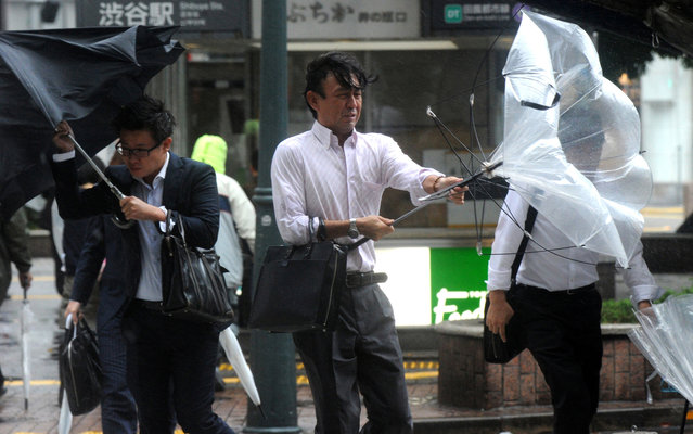 """Japanese businessmen walk against strong wind and rain in Tokyo on October 16, 2013. At least three people died as Typhoon Wipha, the """"strongest in 10 years"""", passed close to Tokyo, causing landslides that swallowed houses on a Japanese island. (Photo by Yoshikazu Tsuno/AFP Photo)"""