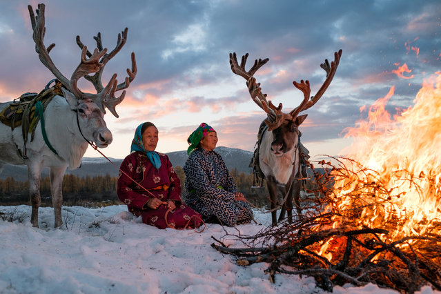 Purev and Buyantogtokh enjoy the warmth of the fire in the snow in Altai Mountains, Mongolia, September 2016. (Photo by Joel Santos/Barcroft Images)