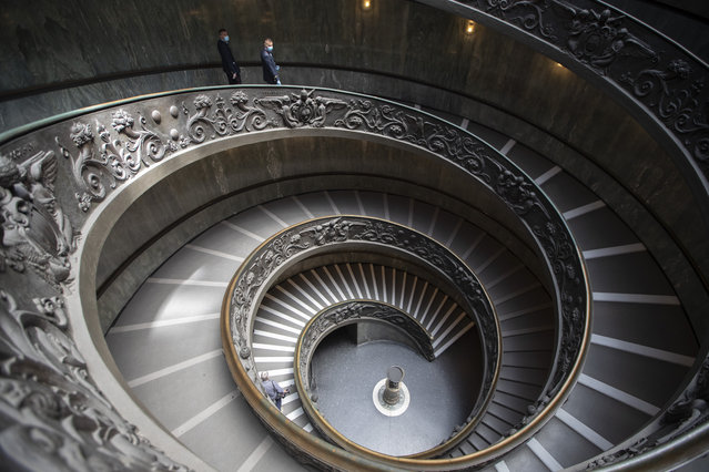 Museum employees, wearing masks to prevent the spread of coronavirus, walk down a staircase designed by Giuseppe Momo in 1932, inspired by the original Bramante staircase designed by Renaissance architect Donato Bramante, as the Vatican Museum reopened, in Rome, Monday, June 1, 2020. The Vatican Museums reopened Monday to visitors after three months of shutdown following COVID-19 containment measures. (Photo by Alessandra Tarantino/AP Photo)