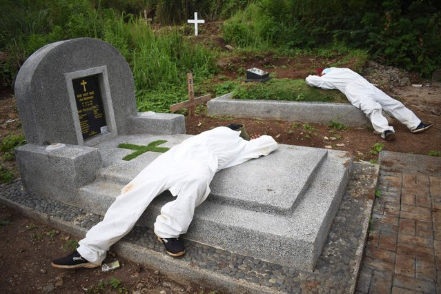 Exhausted grave diggers rest in between funerals at a cemetery designated for Covid-19 victims in Bandung on June 15, 2021, as infection numbers soar in Indonesia. (Photo by Timur Matahari/AFP Photo)