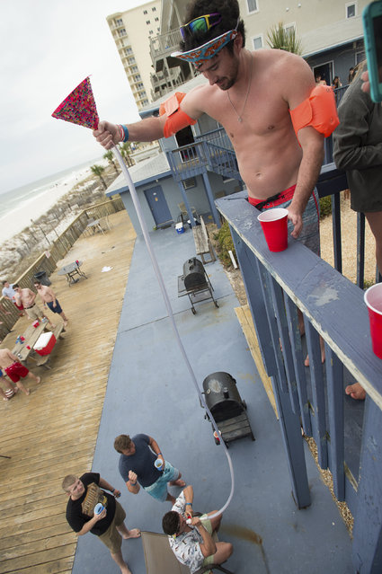 Zack Fox (R) and Taylor Meek of Tarleton State University in Stephenville, Texas, use a beer bong during spring break festivities in Panama City Beach, Florida March 13, 2015. (Photo by Michael Spooneybarger/Reuters)