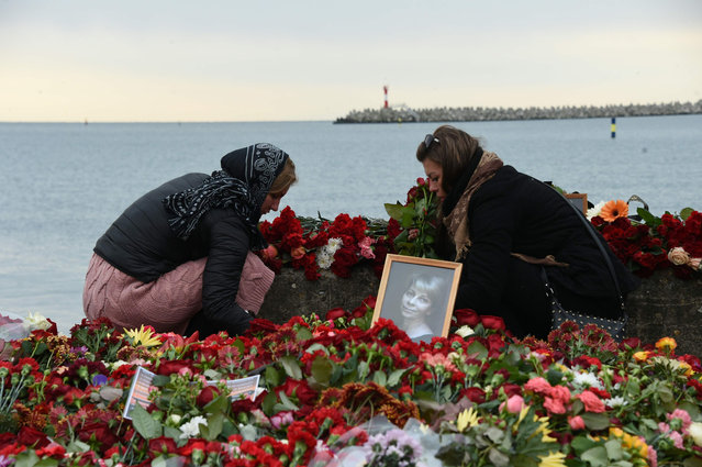 People lay flowers next to a portrait of one of the victims, famous Russian charity activist and founder of the Voters' League Elizaveta Glinka or Dr Liza, at a makeshift memorial at the embankment on the shore of the Black Sea in Sochi, on December 27, 2016, as rescue vessels search the area two days after a military plane carrying 92 people, including dozens of members of the Red Army Choir, crashed in the Black Sea. The main black box of the Syria-bound Russian military plane that crashed into the Black Sea with 92 people onboard has been found in a massive ongoing search operation, authorities said on December 27, 2016. The Tu-154 jet, whose passengers included more than 60 members of the internationally renowned Red Army Choir, was heading to Russia's military airbase in Syria when it went down off the coast of the resort city of Sochi shortly after take-off on December 25. (Photo by Vasily Maximov/AFP Photo)