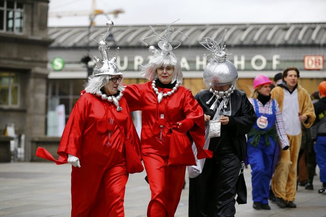 """Female carnival revellers walk in front of the main station during """"Weiberfastnacht"""" (Women's Carnival) in Cologne, Germany February 4, 2016. Women's Carnival marks the start of a week of street festivals, the highlight of the event being """"Rosenmontag"""" (Rose Monday), the final day of the yearly carnival season where mass processions are held. (Photo by Wolfgang Rattay/Reuters)"""
