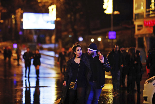 Young people leave from the scene of an attack in Istanbul, early Sunday, January 1, 2017. (Photo by Halit Onur Sandal/AP Photo)