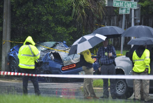 Law enforcement investigators stand on the scene of a fatal car crash on Roosevelt Blvd. in the Ortega neighborhood of Jacksonville, Fla. during the strong winds from Tropical Storm Elsa, Wednesday, July 7, 2021. (Photo by Bob Self/The Florida Times-Union via AP Photo)