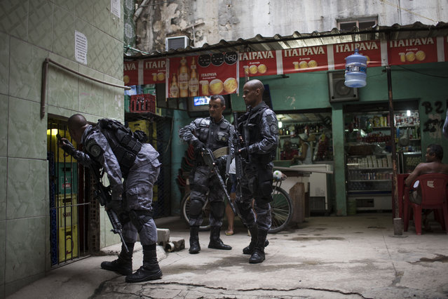 Military police officers search for drugs and weapons at the Roquette Pinto shantytown, part of the Mare slum complex in Rio de Janeiro, Brazil, Wednesday, April 1, 2015. (Photo by Felipe Dana/AP Photo)