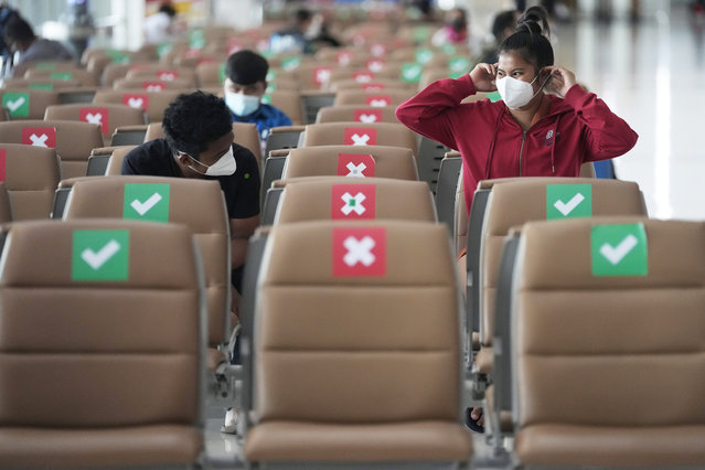 Passengers sit spaced apart while wearing face masks to help curb the spread of the coronavirus at Suvarnabhumi airport in Bangkok, Thailand, Wednesday, July 21, 2021. The Civil Aviation Authority of Thailand has ordered a halt to all domestic flights operating from the most severely affected provinces effective Wednesday. Exceptions are allowed for flights to destinations that are part of a plan that allows vaccinated travelers from abroad to stay for two weeks on popular islands such as Phuket and Samui without quarantine confinement. (Photo by Sakchai Lalit/AP Photo)