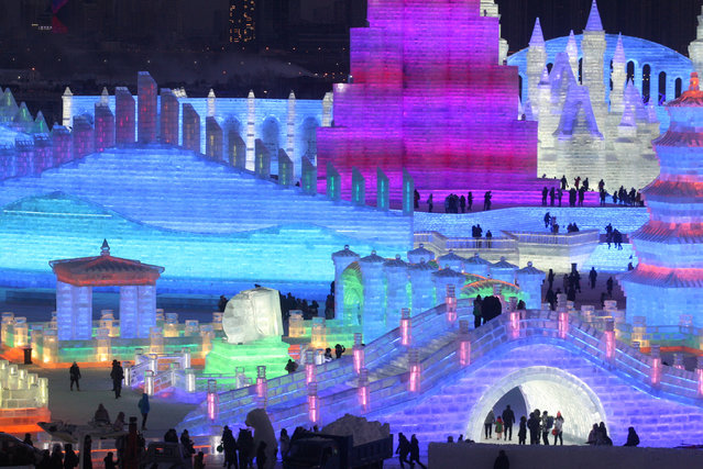 People visit illuminated ice sculptures at the Ice and Snow World park ahead of the Harbin International Ice and Snow Sculpture Festival, in Harbin, Heilongjiang province, China on December 23, 2018. (Photo by Reuters/China Stringer Network)