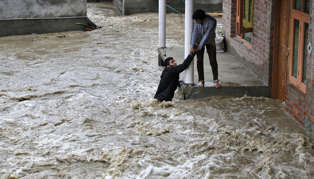 A Kashmiri man stretches his hand to help a local evacuate from a flood affected area in Srinagar, Indian-controlled Kashmir, Monday, March 30, 2015. Hundreds of Kashmiris in both India and Pakistan moved to higher ground Monday as rain-swollen rivers swamped parts of the disputed Himalayan region placed under an emergency flood alert just six months after some 600 people died in flooding that left the region in shambles. (Photo by Mukhtar Khan/AP Photo)