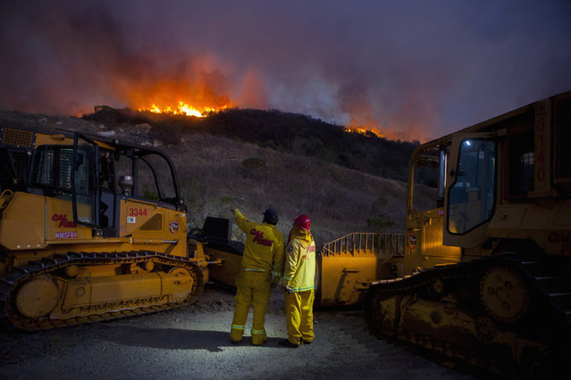 Firefighters battle a blaze, part of the Poinsettia Fire, in San Marcos, May 14, 2014. (Photo by Sam Hodgson/Reuters)