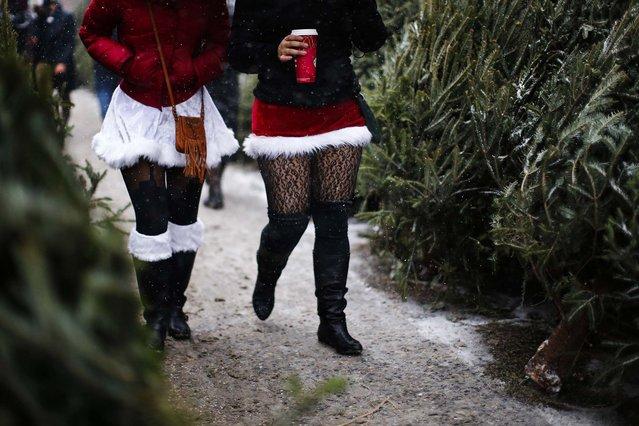 Revelers dressed as Santa Claus walk in the snow during SantaCon in New York. (Photo by Eduardo Munoz/Reuters)