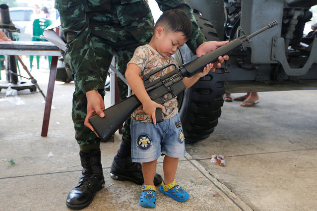 A Thai army soldier gives a weapon to a boy to pose for a picture during Children's Day celebration at a military facility in Bangkok, Thailand January 14, 2017. (Photo by Jorge Silva/Reuters)