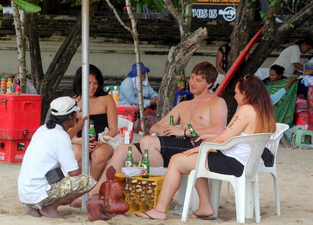 A group of tourists holds their beer while relaxing at Kuta beach on Bali resort island April 14, 2015. Two Islamic parties have proposed legislation that would ban all consumption of alcoholic drinks and bring jail terms of up to two years for offenders in Indonesia, home to the world's largest Muslim population. The proposed legislation banning all alcohol consumption would exempt some locations to protect tourism such as five-star hotels and the resort island of Bali. (Photo by Zul Edoardo/Reuters)