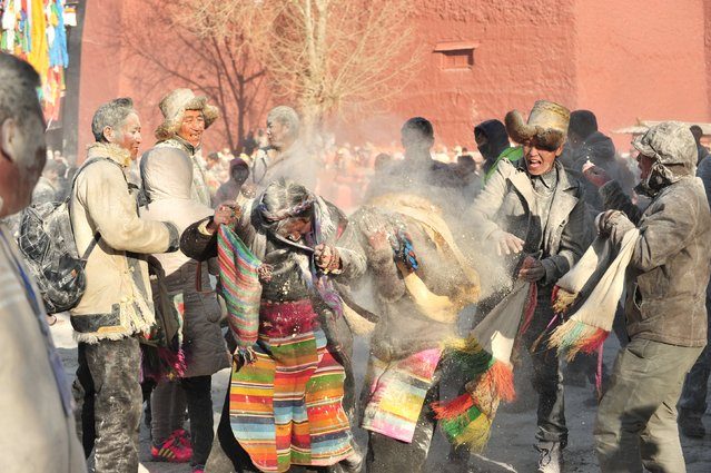 """Tibetans throw """"zanba"""", traditional Tibetan roasted flour, at each other during a zanba fight event to pray for a good harvest in Shigatse, Tibet Autonomous Region, China, February 22, 2016. (Photo by Reuters/China Daily)"""