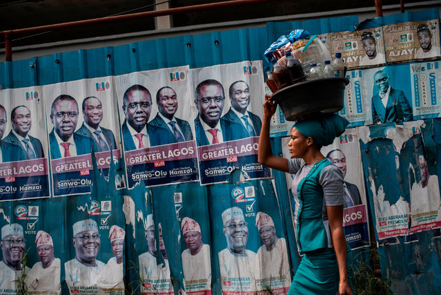 A woman with a large plastic bucket filled with drinks and food on her head passes by a wall covered with posters of presidential candidate Atiku Abubakar of the Peoples Democratic Party (PDP), the official opposition party, in Lagos on February 11, 2019. Nigerians will participate in the national elections on February 16 where current President Mohammadu Buhari is seeking re-election for the Nigerian ruling party All Prgressives Congress (APC). (Photo by Stefan Heunis/AFP Photo)