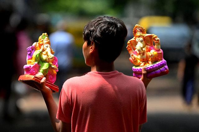 A boy carries idols of the elephant-headed Hindu god Ganesha outside a workshop ahead of the Ganesh Chaturthi festival in New Delhi on September 6, 2021. (Photo by Money Sharma/AFP Photo)