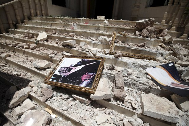 A picture of Saudia Arabia's King Salman bin Abdulaziz lies amidst debris at the damaged entrance to the headquarters of the Saudi Cultural Center in Sanaa, caused by an April 20 air strike that hit a nearby army weapons depot, in Sanaa April 21, 2015. (Photo by Mohamed al-Sayaghi/Reuters)