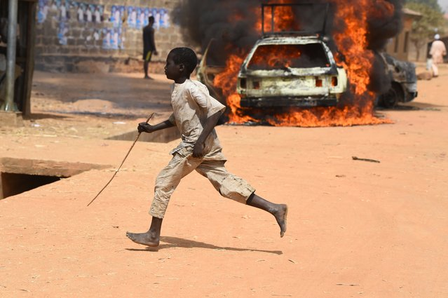 A boy run as cars are set on fire following deadly clashes between supporters of the ruling All Progressives Congress (APC) and the opposition Peoples Democratic Party (PDP) at Kofa in Bebeji district of Kano, economic nerve centre of northern Nigeria, on February 22, 2019. Two people were killed, while 40 vehicles, 12 motorcycles and houses were burn following bloody clashes  between supporters of the ruling All Progressives Congress (APC) and the opposition Peoples Democratic Party (PDP) in Kofa town, Bebeji district of Kano, northeast Nigeria ahead of tomorrow's rescheduled presidential election. (Photo by Pius Utomi Ekpei/AFP Photo)