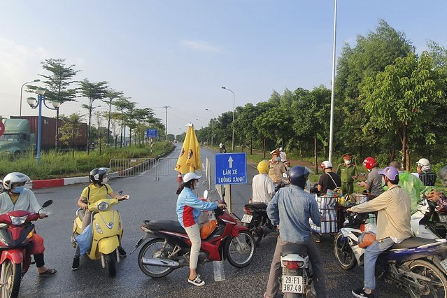 People are turned away at a checkpoint at an entrance to Hanoi, Vietnam, Saturday, July 24, 2021. Vietnam announced a 15-day lockdown in the capital Hanoi starting Saturday as a coronavirus surge spread from the southern Mekong Delta region. (Photo by Hieu Dinh/AP Photo)