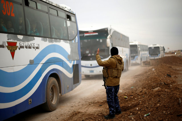 An Iraqi soldier waves as buses transport displaced Iraqs returning to their homes in east Mosul after it was retaken from Islamic State militants January 25, 2017. (Photo by Ahmed Jadallah/Reuters)