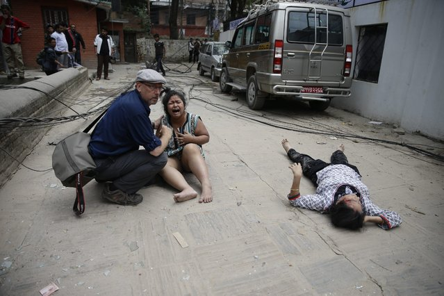 A man comforts a woman next to a seriously injured person on the ground after an earthquake hit Nepal, in Kathmandu, Nepal, 25 April 2015. (Photo by Narendra Shrestha/EPA)