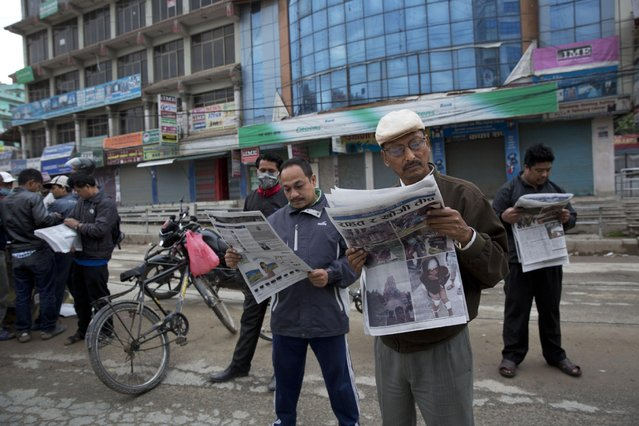 Locals read morning edition of a newspaper as they stand in the middle of a street in Kathmandu, Nepal, Monday, April 27, 2015. (Photo by Bernat Armangue/AP Photo)