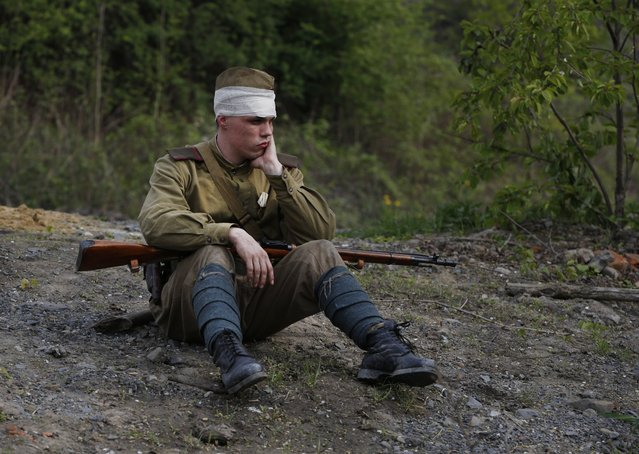 A World War II re-enactor dressed as Red Army soldiers rests after a staged battle to mark the liberation of the city of Ostrava by Red Army from the Nazi invaders in 1945, Czech Republic, Thursday, April 30, 2015. (Photo by Sergei Grits/AP Photo)