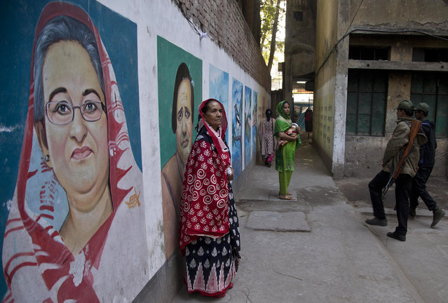 Bangladeshi women stand next to a mural displaying portraits of Bangladesh Prime Minister Sheikh Hasina, left, and others after casting their votes at a polling station in Dhaka, Bangladesh, Sunday, December 30, 2018. Voting was underway Sunday in Bangladesh's contentious parliamentary elections, seen as a referendum on what critics call Prime Minister Sheikh Hasina's increasingly authoritarian rule, amid complaints from both ruling party and opposition activists of attacks on supporters and candidates. (Photo by Anupam Nath/AP Photo)