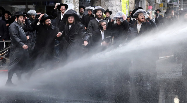 Israeli police spray water towards ultra-Orthodox Jews during a protest against Israeli army conscription, in an ultra-Orthodox Jewish neighbourhood of Jerusalem, on February 9, 2017. Many ultra-Orthodox oppose military service for their young men because they believe it exposes them to influences and temptations not found in the insular world of prayer and religious study. (Photo by Thomas Coex/AFP Photo)