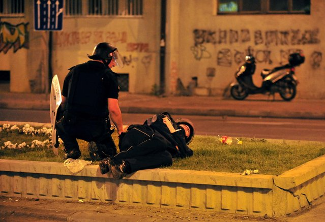 A police officer tries to help an injured colleague after clashes with protesters at a protest in Skopje Macedonia, late Tuesday, May 5, 2015. Violent clashes broke out late Tuesday at a demonstration in the Macedonian capital Skopje protesting the 2011 death of a 22-year-old beaten by police during post-election celebrations. (Photo by Vangel Tanurovski/AP Photo)