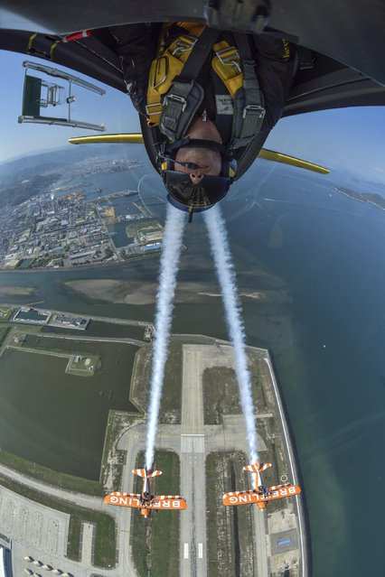 The Breitling Wing Walking team fly in formation with Japanese Red Bull Air Race Pilot Yoshihide Muroya, who is inverted, flying his Breitling Extra 300L aircraft over the Seto Inland Sea close to Hiroshima, Japan, on Saturday, May 2, 2015. (Photo by Katsuhiko Tokunaga/AP Images/Breitling)