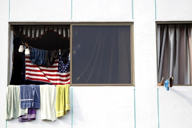The U.S flag is seen in one of the windows of an old hotel used as a provisional shelter in Paso Canoas, border with Costa Rica, in Panama March 21, 2016. (Photo by Carlos Jasso/Reuters)