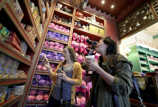 """Guests look at a display of candy inside the Honeydukes sweets shop in Hogsmeade Village during a soft opening and media tour of """"The Wizarding World of Harry Potter"""" theme park at the Universal Studios Hollywood in Los Angeles, California in this picture taken March 22, 2016. (Photo by Kevork Djansezian/Reuters)"""