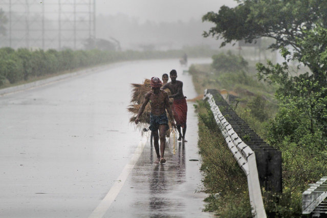 """Villagers move to safer places amidst gusty winds ahead of the landfall of cyclone Fani on the outskirts of Puri, in the Indian state of Odisha, Friday, May 3, 2019. Indian authorities have evacuated hundreds of thousands of people along the country's eastern coast ahead of a cyclone moving through the Bay of Bengal. Meteorologists say Cyclone Fani was expected to make landfall on Friday with gale-force winds of up to 200 kilometers (124 miles) per hour likely starting Thursday night. It warned of """"extremely heavy falls"""" over parts of the state of Odisha and its southern neighbor Andhra Pradesh. (Photo by AP Photo)"""