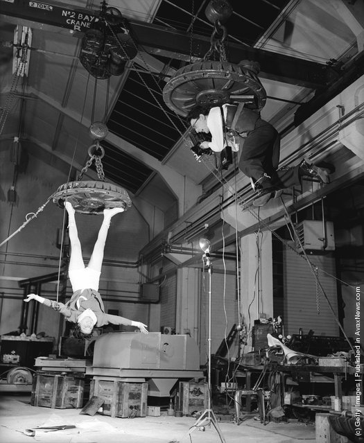 Fox Photos photographer Derek Berwin is hoisted up on an electromagnet at the Boxmag works in Birmingham, in order to take a photograph of typist Kathleen Reddington who is similarly suspended, December 1957