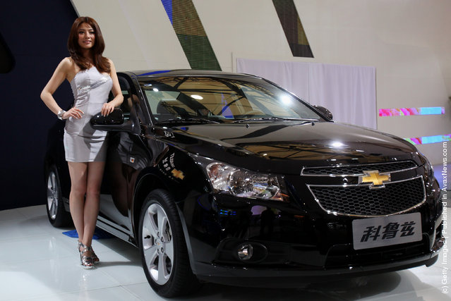 A model stands beside the Asia premiere display of Chevrolet Cruze