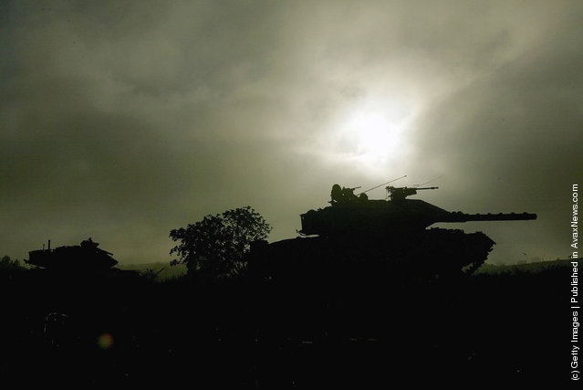 Israeli army Merkava tanks are silhouetted against the morning sun