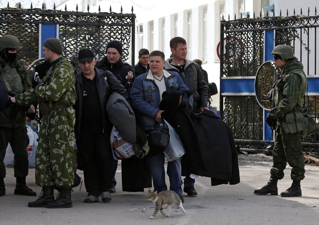 People, believed to be Ukrainian servicemen, carry their belongings as they walk past armed men, believed to be Russian servicemen, on their way out of the naval headquarters after it was taken over by pro-Russian forces in Sevastopol, March 19, 2014. (Photo by Vasily Fedosenko/Reuters)